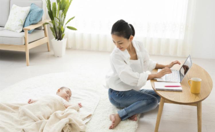 新生児と在宅ワークをするママ