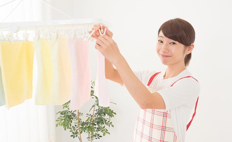 梅雨の時期に室内干しをする主婦のイメージ画像